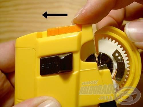 A szerkezet tetején található narancsszínű gombot toljuk el balra, és addig tartsuk ebben a helyzetben, amíg a gép fel nem tekerte a kívánt számú menetet a horog szárára. Ha a gombot elengedjük, automatikusan visszaáll az eredeti pozícióba úgy, hogy a tárcsa vágását mindig a megfelelő (függőlegesen) pozícióba állítja