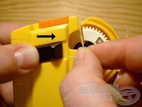 Toljuk jobbra a fekete gombot, és a horgot kivehetjük. Kézzel szorítsuk meg a kötést. Ezzel elkészült a horogkötés