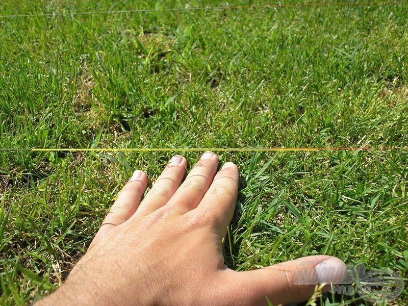 A kép optikai csalódás, az ujjaim és a Leadcore közti távolság valójában kb. 5-6 cm volt. Biztos támpontként szolgál az árnyék, illetve az általam behúzott sárga vonal, amely a vízszintes egyenest jelöli ki. A Sufix modell ennél a próbánál nem feküdt teljes hosszban